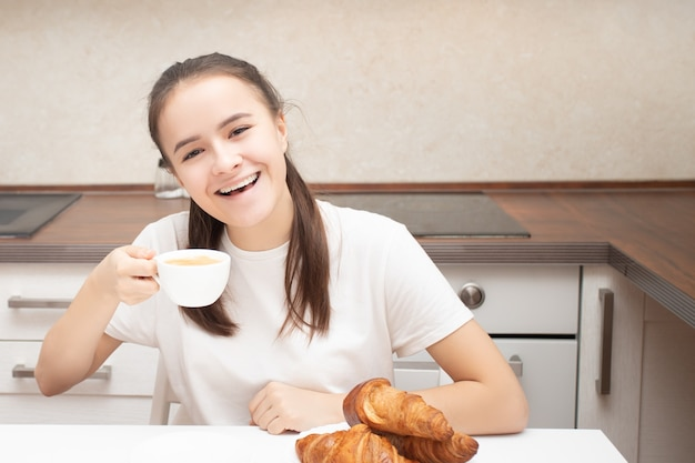 European girl in the morning at home having breakfast with croissants, drinking coffee, smiling.