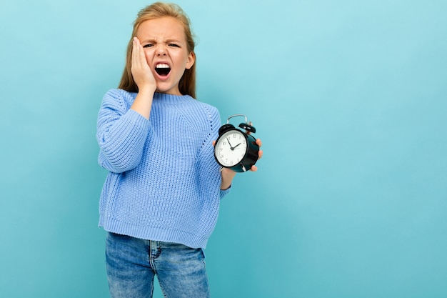 European girl overslept and holds an alarm clock on light blue with copyspace