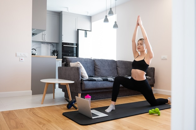 European girl practicing yoga and stand in asana pose on fitness mat. young pretty blonde woman with closed eyes wear sportswear. concept of sport activity at home. interior of studio apartment