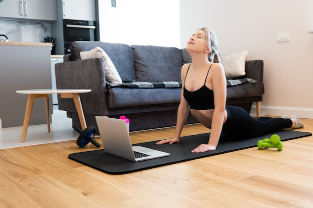European girl practicing yoga and standing in asana pose on fitness mat. young beautiful blonde woman with closed eyes wear sportswear. concept of sport activity at home. interior of studio apartment