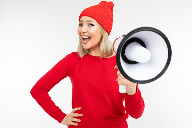 European girl in red clothes with a loudspeaker in her hands screaming on a white