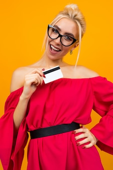 European girl in a red dress with a credit card