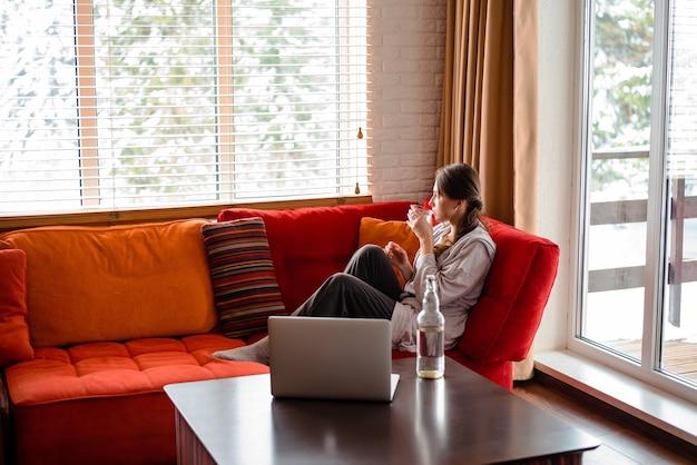 유럽 소녀는 소파에 앉아 집에서 유리로 물을 마십니다. 사려깊은 젊은 여성은 평상복을 입는다. 현대 아파트의 거실 인테리어입니다. 테이블에 노트북 컴퓨터와 병