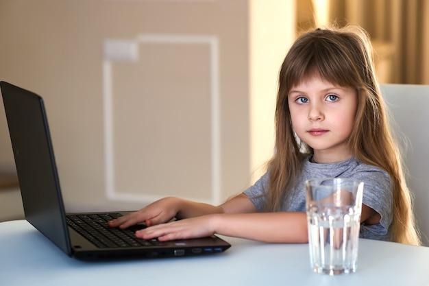 집에서 홈 스쿨링하는 동안 온라인 연구를 위해 노트북을 사용하는 유럽 소녀.