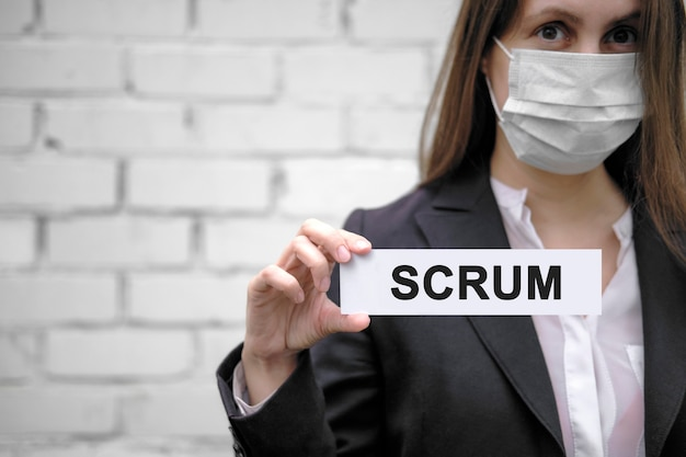 A european girl wearing a medical mask holds a sign with the inscription scrum