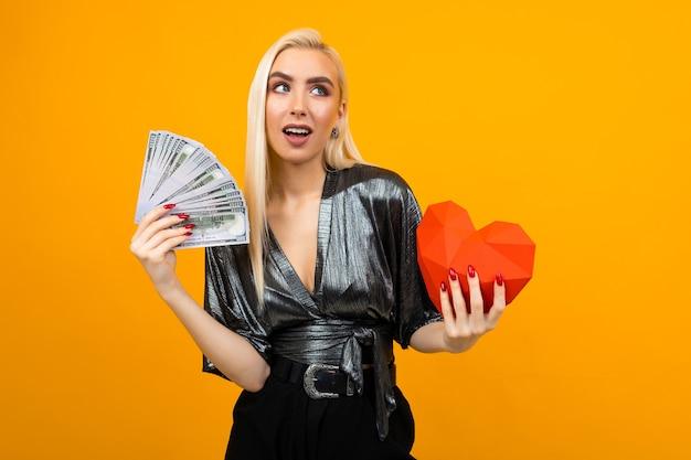 Европейская девушка с большим количеством денег и формой сердца на желтом