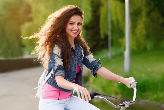 European girl with beautiful smile rides bicycle in the city in the summer.
