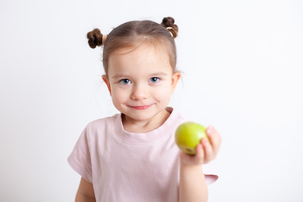 European girl with blue eyes holds a green apple in her hand