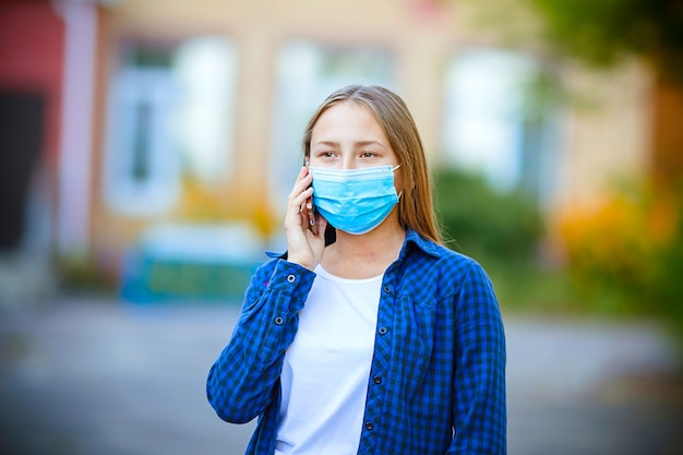 European girl with dark hair in medical flu mask for the prevention of talking on the phone on the street. concept of protection against viral infection and urban smog.