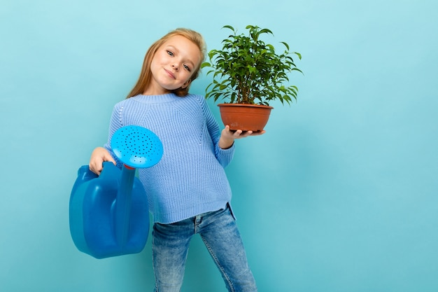 European girl with a watering can and a plant in her hands on a light blue wall.