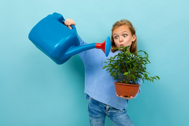 European girl with a watering can and a plant in her hands on light blue