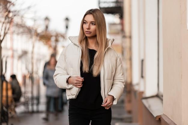 セーターの黒のジーンズでファッショナブルな白いジャケットを着たヨーロッパの魅力的な若い女性のブロンドは、ヴィンテージの建物の近くに屋外に立っています。魅力的な現代の女の子モデルが通りを歩きます。ファッション。