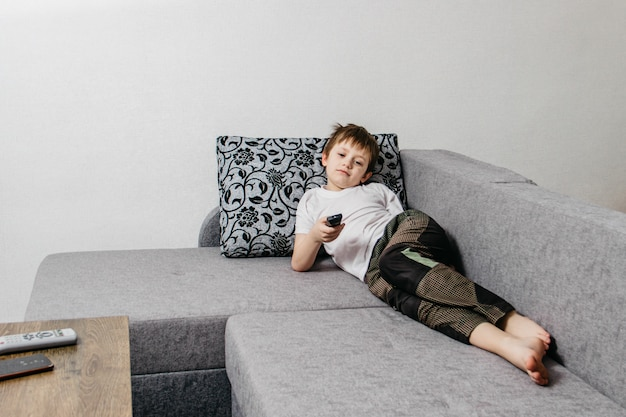 European guy holds a remote control in his hand while lying on a sofa during isolation or a weekend