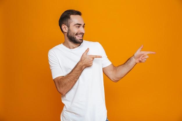 Европейский парень в футболке показывает пальцем в сторону стоя, изолированный на желтом