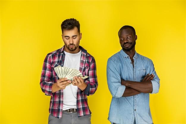 Европейский парень считает деньги, а афроамериканец смотрит на него