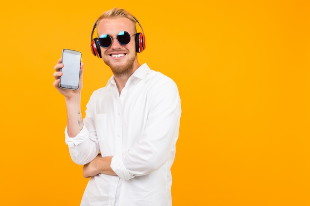 European guy in a white shirt and sunglasses listens to music in large headphones and shows the phone screen on yellow.