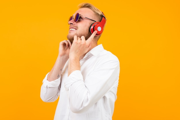 European guy in a white shirt and sunglasses listens to music in large headphones on yellow.