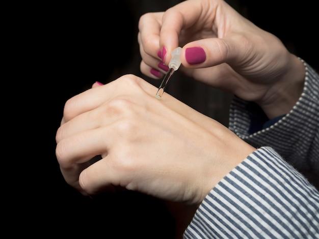 アラビアの香油を持つ女性のヨーロッパの手。