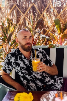European handsome bearded man drinks mango smoothie in summer cafe, tropical wall behind.