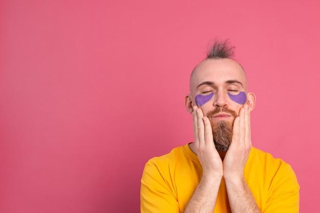 노란색 티셔츠와 분홍색에 보라색 눈 패치 마스크에 유럽의 잘 생긴 수염 난된 남자