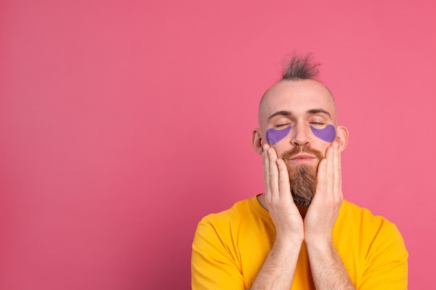 European handsome bearded man in yellow t-shirt and purple eye patches mask on pink