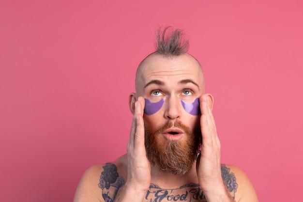 Uomo in topless tatuato bello barbuto europeo con maschera di bende sull'occhio viola in posa per la fotocamera sul rosa