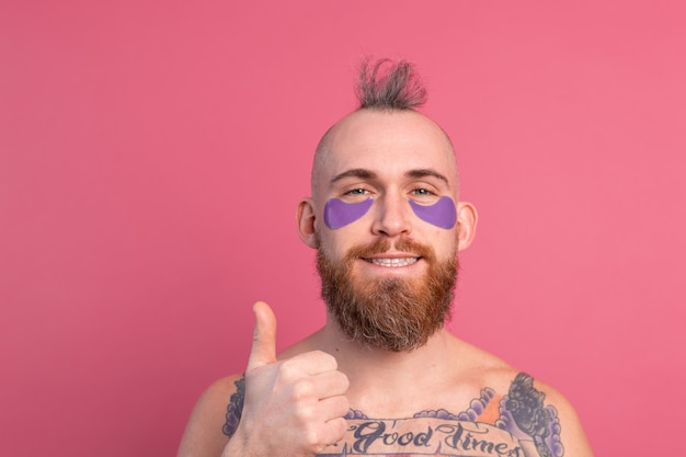 European handsome bearded tattooed topless man with purple eye patches mask posing to camera on pink