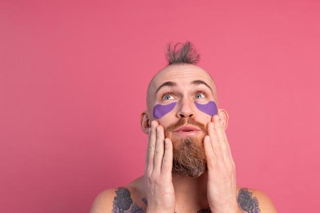 분홍색에 카메라에 포즈 보라색 눈 패치 마스크와 유럽의 잘 생긴 수염 문신 토플리스 남자