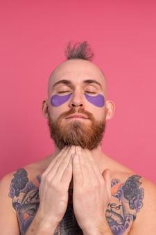 ピンクのカメラにポーズをとる紫色の眼帯マスクを持つヨーロッパのハンサムなひげを生やした入れ墨トップレスの男