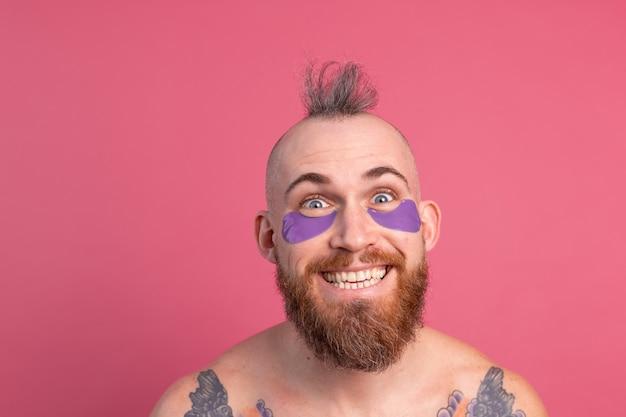Европейский красавец с бородой и татуировкой топлес с фиолетовой маской для глаз позирует перед камерой на розовом