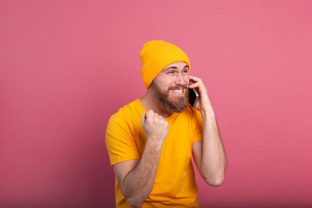 자랑스럽게 비명을 지르고 승리와 성공을 축하하는 스마트 폰에 대해 이야기하는 유럽의 잘 생긴 남자가 분홍색에 매우 흥분했습니다.