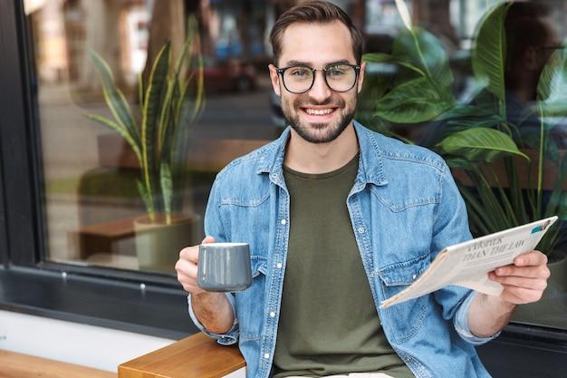 Европейский счастливый человек в джинсовой рубашке и очках читает газету с чашкой кофе в кафе на открытом воздухе