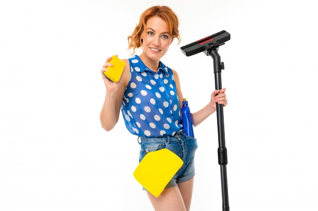 European housewife with cleaning products and a vacuum cleaner in her hands on a white wall