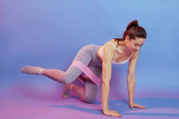 무릎에 저항 밴드가있는 네 발로 유럽 여성, 한쪽 다리를 옆으로 잡고, 여성은 세련된 운동복을 입고 컬러 배경 위에 절연 실내에서 운동합니다.