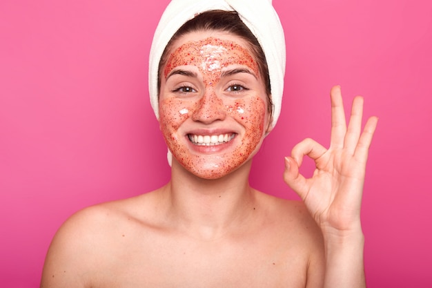 European lady with cleansing mask on face, shows okay sign, has toothy smile, wears white towel, has naked body