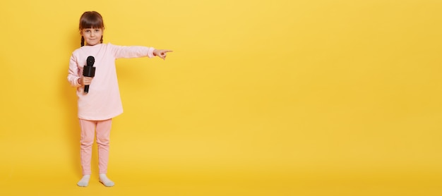 European little girl with microphone looks at camera while holding mic, points index finger aside at empty space for advertisement or promotion, charming vocalist presenting something at yellow wall.