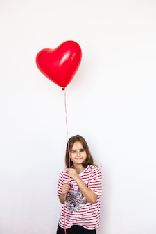 European-looking girl on a white background holding a heart-shaped balloon,