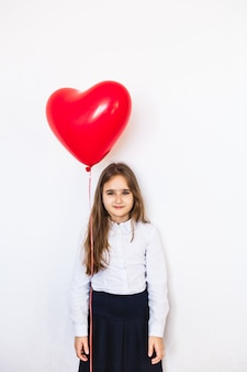 European-looking girl on a white background holding a heart-shaped balloon