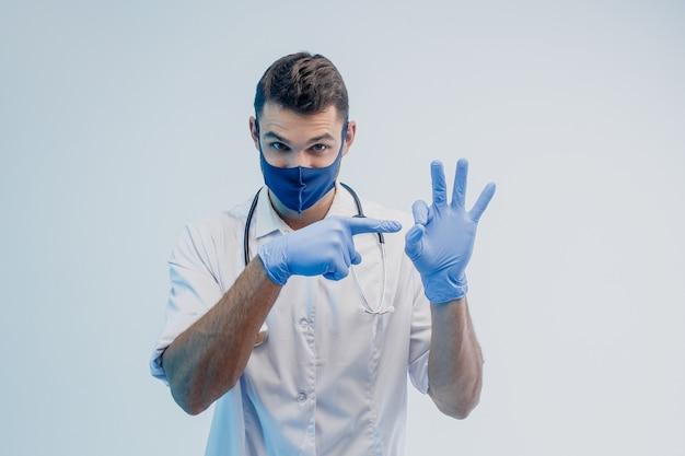 Европейский мужчина-врач в защитной маске и латексных перчатках указывает пальцем и показывает жест ок. молодой человек со стетоскопом и носить белое пальто. серый фон с бирюзовым светом. студийная съемка