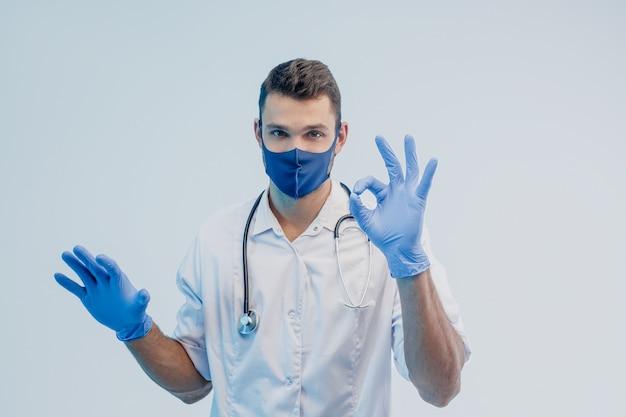 Европейский мужчина-врач в защитной маске и латексных перчатках показывает жест ок. молодой человек со стетоскопом в белом халате. изолированные на сером фоне с бирюзовым светом. студийная съемка. скопируйте пространство.