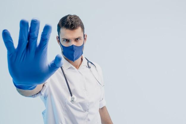 Европейский мужчина-врач в защитной маске и латексных перчатках показывает стоп-жест. молодой человек со стетоскопом в белом халате. изолированные на сером фоне с бирюзовым светом. студийная съемка. копировать пространство