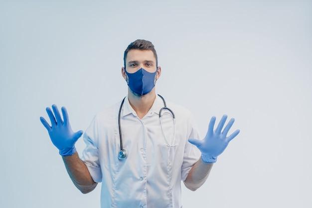 Европейский врач-мужчина в защитной маске и латексных перчатках. молодой человек со стетоскопом в белом халате. изолированные на сером фоне с бирюзовым светом. студийная съемка. скопируйте пространство.