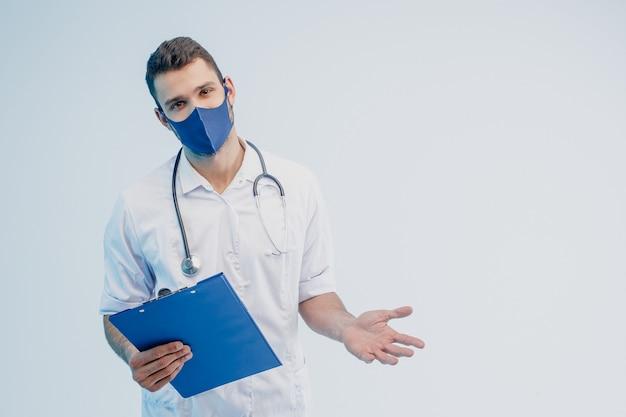 Европейский мужской доктор в защитной маске держит буфер обмена. молодой человек со стетоскопом в белом халате. изолированные на сером фоне с бирюзовым светом. студийная съемка. скопируйте пространство.