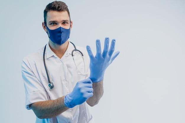 Европейский мужчина-врач в защитной маске надевает латексные перчатки на руки. молодой человек со стетоскопом в белом халате. изолированные на сером фоне с бирюзовым светом. студийная съемка. скопируйте пространство.
