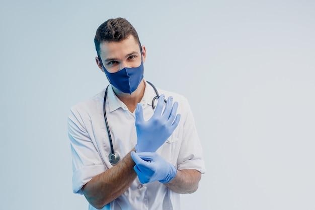 Европейский мужчина-врач в защитной маске надевает латексные перчатки. молодой человек со стетоскопом в белом халате. изолированные на сером фоне с бирюзовым светом. студийная съемка. скопируйте пространство.