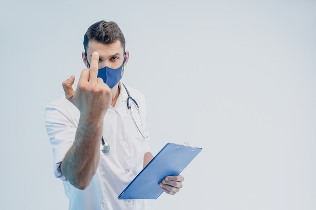 Европейский мужчина-врач в защитной маске показывает средний палец. буфер обмена удержания молодого человека. человек со стетоскопом в белом халате. серый фон с бирюзовым светом. студийная съемка. скопируйте пространство.