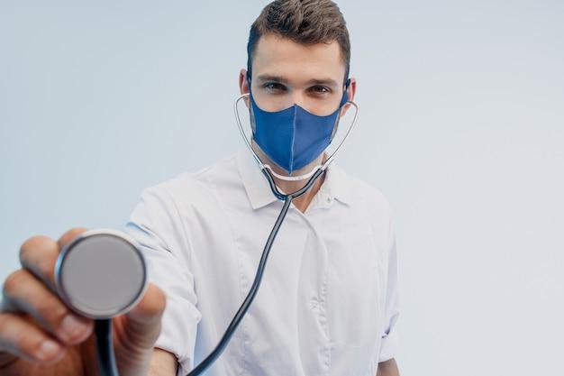 Европейский мужчина-врач в защитной маске с помощью стетоскопа. молодой человек в белом халате. изолированные на сером фоне с бирюзовым светом. студийная съемка. скопируйте пространство.