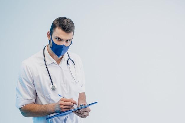 Европейский мужчина-врач в защитной маске пишет что-то в буфере обмена. человек со стетоскопом носит белое пальто. человек со скептическим лицом. серый фон с бирюзовым светом. студийная съемка. копировать пространство