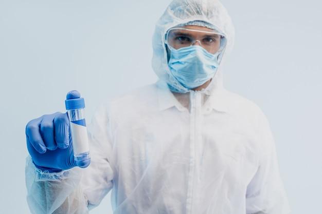 Covid-19ワクチンを示すヨーロッパの男性医師。白衣、ゴーグル、保護マスク、ラテックス手袋を着用した男性。コロナウイルスとの戦いの概念。ターコイズブルーの光と灰色の背景。スタジオ撮影