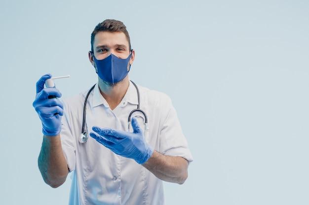 Европейский мужской доктор показывает ингалятор. молодой человек со стетоскопом в белом халате, защитной маске и латексных перчатках. изолированные на сером фоне с бирюзовым светом. студийная съемка. скопируйте пространство.